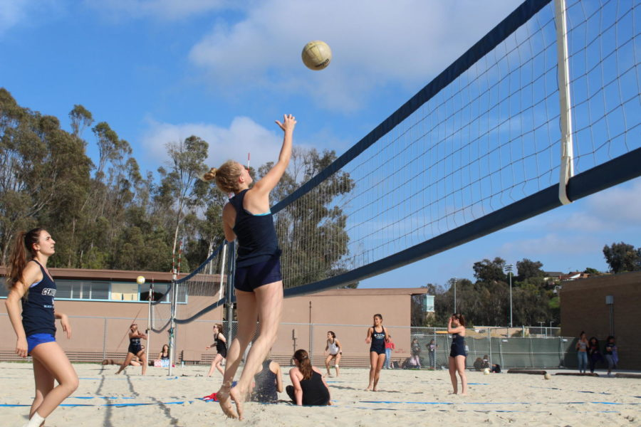 Junior Natalie Dhus jumps up to poke the ball.