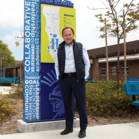 Olivero stands with the Welcome sign in the quad.